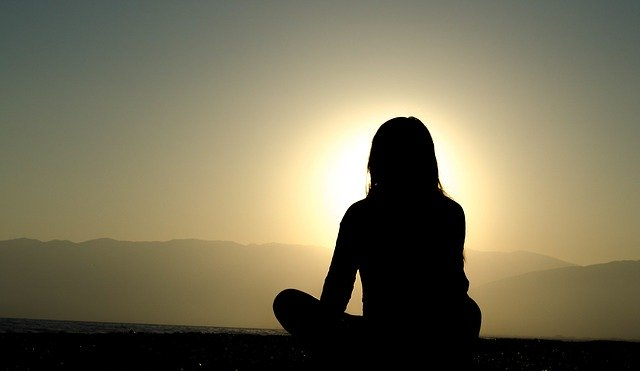 femme méditant pendant un coucher de soleil