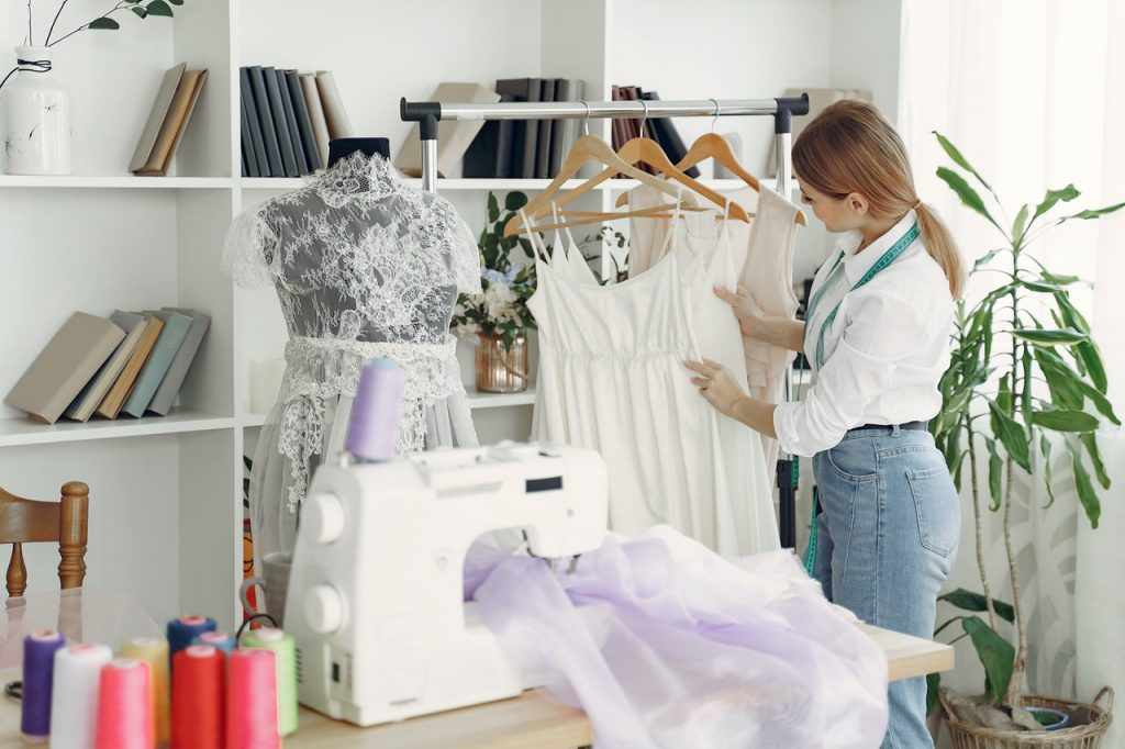 Femme créatrice, styliste, créant des vêtements, robes, tissus dans machine à coudre en préparation