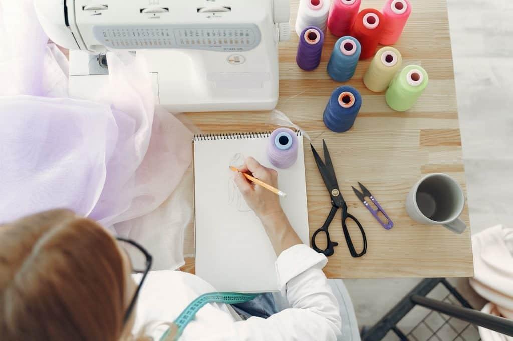 Femme styliste dessinant devant sa machine à coudre et des bobines de fils