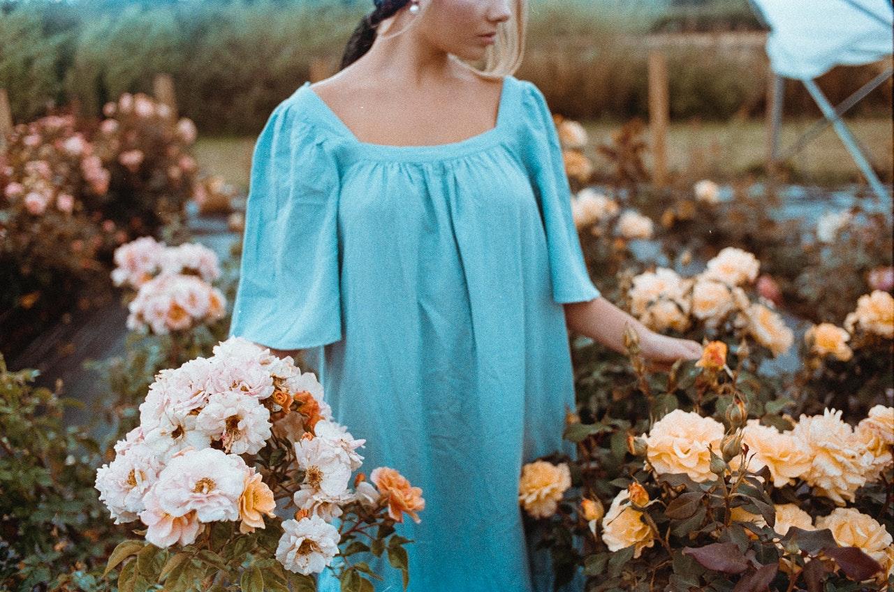Femme portant une robe bleu en lin et ramassant des fleurs