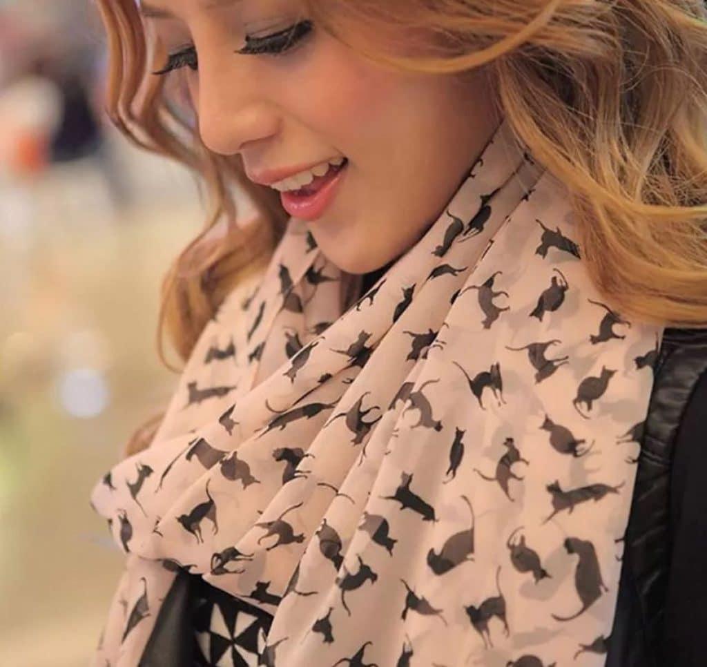 Femme blonde souriante, portant un foulard aux motifs chat
